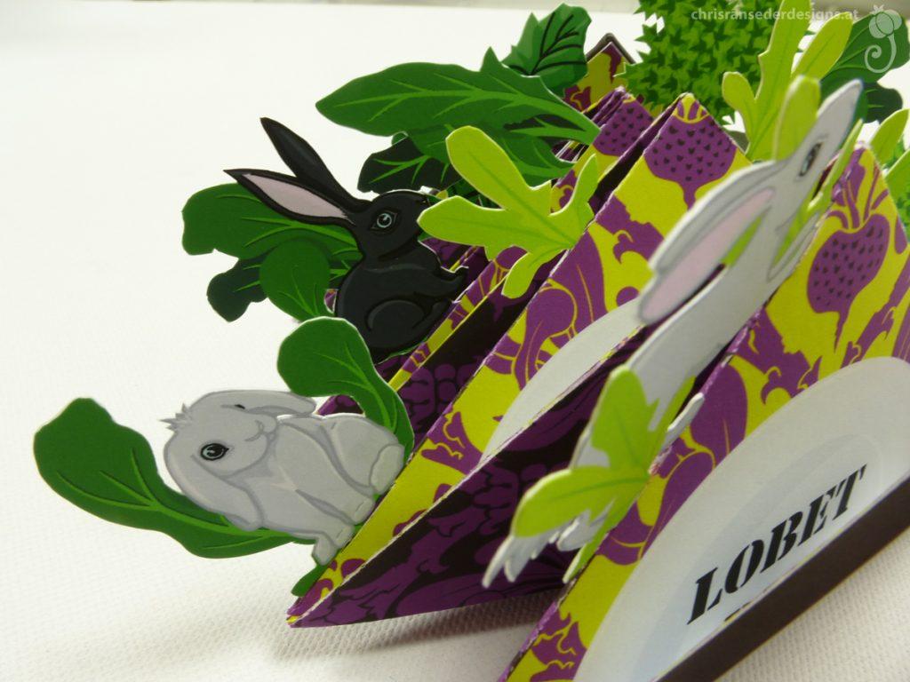 Black and white rabbits amid green turnip-leaves. | Schwarze und weiße Hasen zwischen grünen Rübenblättern.