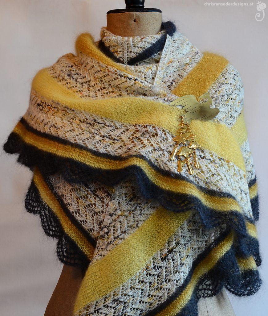 White/yellow speckled knitted scarf with yellow and grey stripes. | Weiß-Gelb gesprenkeltes gestricktes Tuch mit gelben und grauen Streifen.