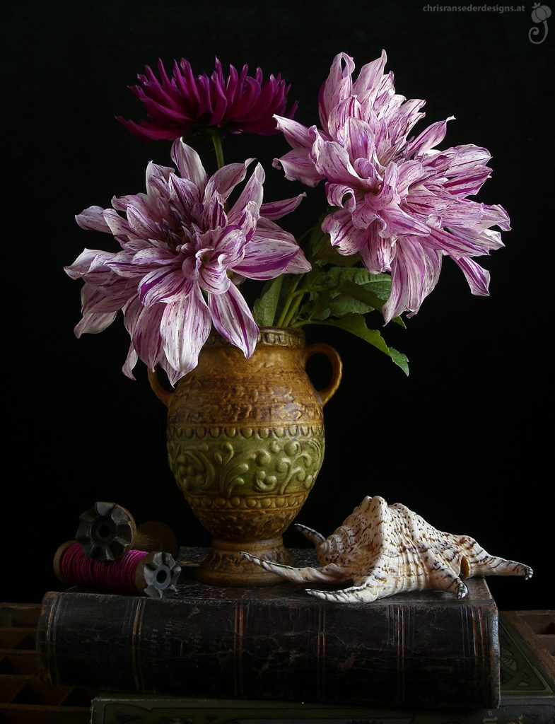 Still life of 3 dahlias in a brown jug placed on a pile of old books. | Sillleben mit 3 Dahlien in einem braunen Krug, der auf einem Bücherstapel steht.