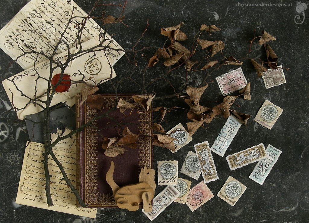 Still life with dry twig, book and old stamps. | Stilleben mit trockenem Zweig, Buch und historischen Briefmarken.