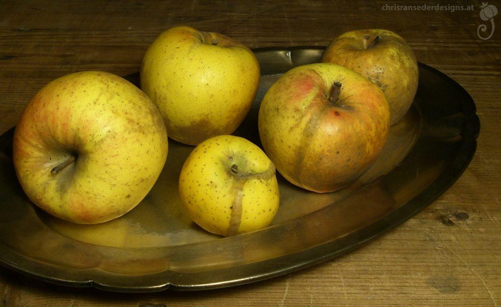 Oval, silver platter with five yellow apples. | Ovale, silberne Vorlegeplatte mit fünf gelben Äpfeln.