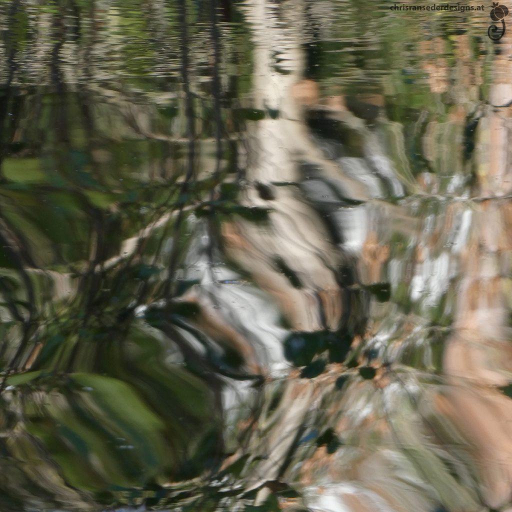 Bewegte Wasseroberfläche in der sich Bäume spiegeln.