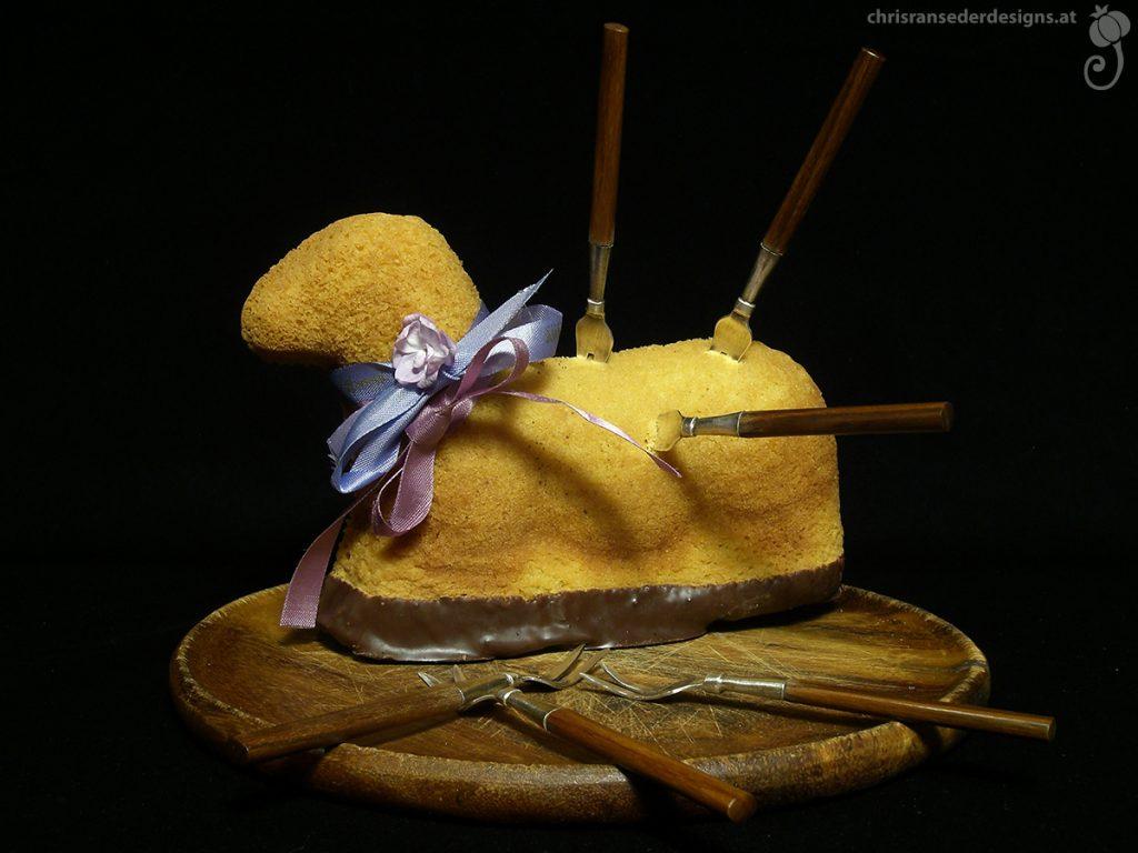 Still life of a lamb-shaped cake stuck with forks, placed on a wooden platter. | Stillleben mit lammförmigen Kuchen in dem Gabeln stecken, serviert auf einem Holzteller.