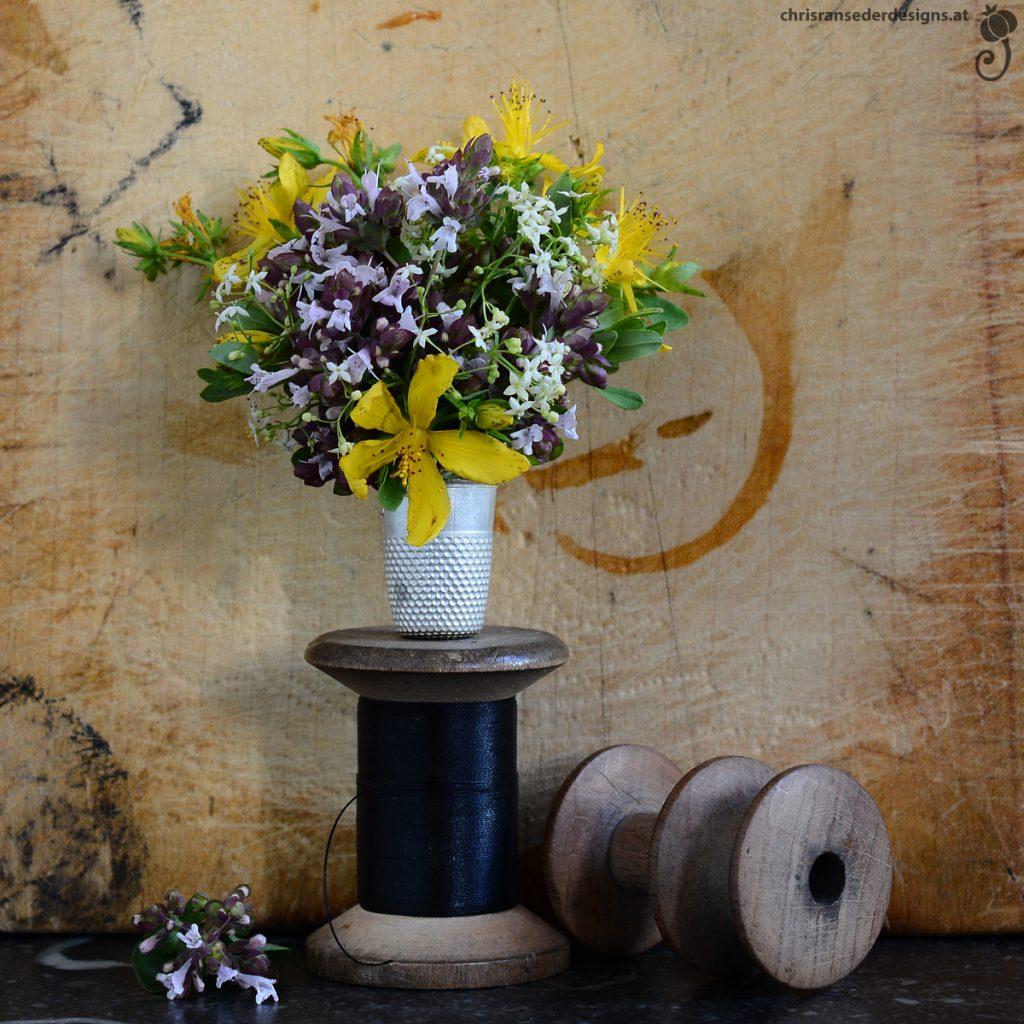 Bouquet of yellow and pale lilac coloured wildflowers in a thimble balanced on a spool. | Strauß aus gelben und blasslila Wildblumen in einem Fingerhut, der auf einer Zwirnspule steht.)