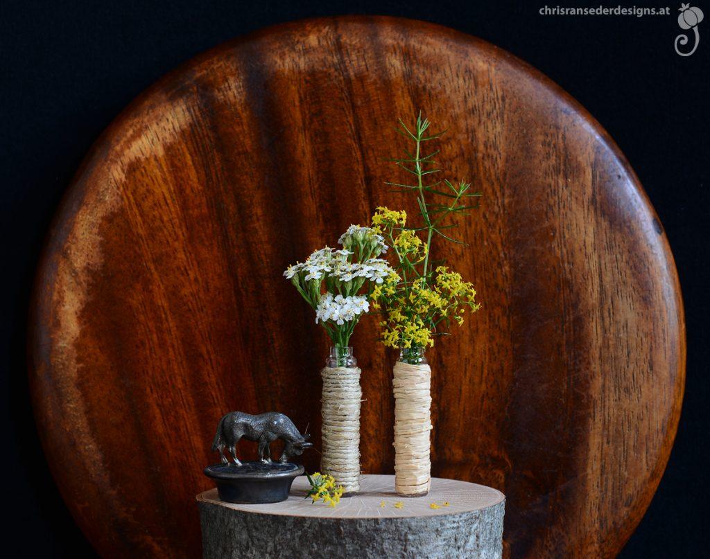 Bouquet of white and yellow wildflowers in twine covered vials of almond essence. Metall bottle stopper with donkey on top. | Strauß aus weißen und gelben Wildblumen in Fläschchen für Mandelessenz, daneben ein Flaschenverschluss aus Metall mit Eselfigur.