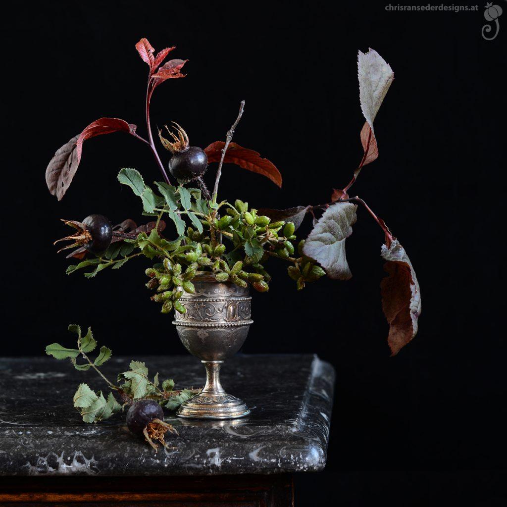 Bouquet of rosehips, berries and leaves arranged in an silver eggcup.   Arrangement aus Hagebutten, Beeren und Blättern in einem silbernen Eierbecher.
