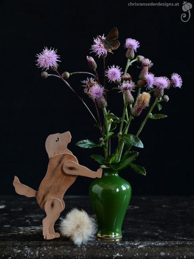Green vase with a bunch of thistles. A wooden toy dog stands on its hind legs and barks at a butterfly sitting on the topmost flower.   Grüne Vase mit Ackerkratzdisteln. Ein hölzerner Spielzeughund steht auf den Hinterbeinen und verbellt einen Schmetterling, der auf der obersten Blüte sitzt.