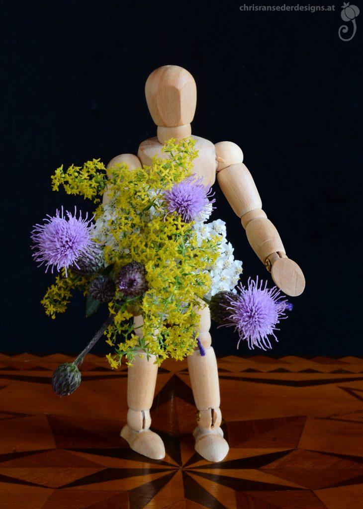 Lay figure for artists holding a bouquet.   Kleine Gliederpuppe, die Blumenstrauß hält.